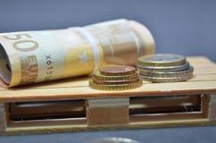 Billetes de banco y dinero euro de la moneda en la plataforma Fotos de archivo libres de regalías