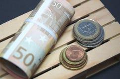 Billetes de banco y dinero euro de la moneda en la plataforma Imagen de archivo