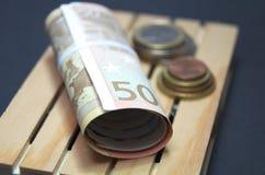 Billetes de banco y dinero euro de la moneda en la plataforma Fácil para el transporte Imágenes de archivo libres de regalías