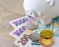 Billetes de banco y monedas checos de la corona con la hucha Fotos de archivo libres de regalías