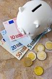 Billetes de banco y monedas euro con la hucha Fotografía de archivo libre de regalías