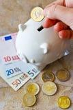 Billetes de banco y monedas euro con la hucha Foto de archivo