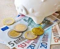 Billetes de banco y monedas euro con la hucha Imagen de archivo libre de regalías