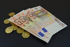 Billetes de banco y monedas euro en fondo negro Fotos de archivo libres de regalías