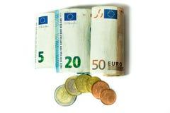 Billetes de banco y monedas euro en un fondo blanco imagen de archivo libre de regalías