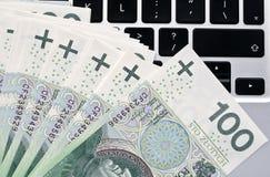 Billetes de banco y ordenador portátil polacos Foto de archivo