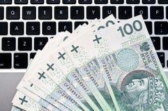 Billetes de banco y ordenador portátil polacos Imagen de archivo