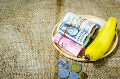 Billetes de banco y plátano en bandeja de madera Fotografía de archivo libre de regalías