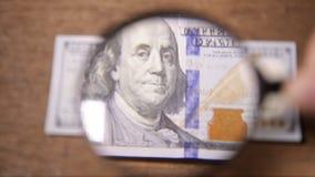 Billetes de dólar americanos de la moneda una a través de una lupa metrajes