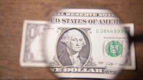 Billetes de dólar americanos de la moneda una a través de una lupa almacen de metraje de vídeo
