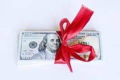 100 billetes de dólar con la cinta roja en un fondo blanco Fotos de archivo libres de regalías