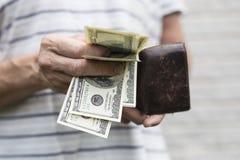 100 billetes de dólar con una cartera llevada vieja fotos de archivo