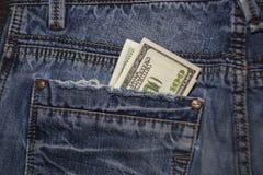 Billetes de dólar del americano 100 en el bolsillo trasero de tejanos Foto de archivo
