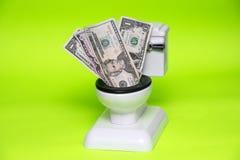 Billetes de dólar dentro del retrete en fondo verde imagen de archivo