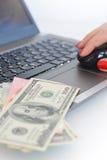 Billetes de dólar en un teclado del ordenador portátil Imagen de archivo