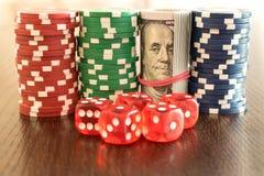 100 billetes de dólar entre las fichas de póker y los dados En TA de madera Fotos de archivo libres de regalías