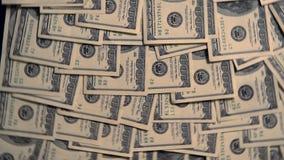 Billetes de dólar múltiples de los E.E.U.U. 100 que cubren una tabla almacen de video