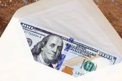 Billetes de dólar o dinero con el sobre Imagen de archivo