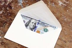 Billetes de dólar o dinero con el sobre Foto de archivo