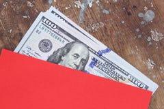 Billetes de dólar o dinero con el sobre rojo Fotografía de archivo