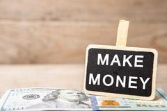 Billetes de dólar, pizarra con el texto y x22; HAGA MONEY& x22; imagen de archivo libre de regalías
