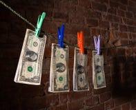 Billetes de dólar que cuelgan en una cuerda Fotos de archivo libres de regalías