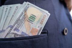 100 billetes de dólar que se pegan hacia fuera del bolsillo de la camisa fotos de archivo
