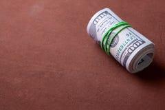100 billetes de dólar torcidos en el tubo y atados con una banda elástica Foto de archivo