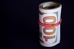 Billetes de dólar torcidos en rollo en fondo oscuro fotos de archivo libres de regalías
