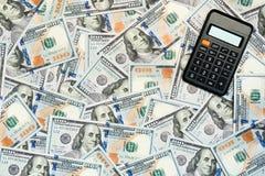 100 billetes de dólar y calculadoras Fotografía de archivo libre de regalías