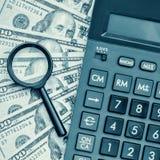 Billetes de dólar con una calculadora y una lupa Imagenes de archivo