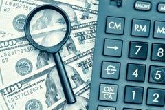 Billetes de dólar con una calculadora y una lupa Imagen de archivo libre de regalías