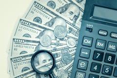 Billetes de dólar con una calculadora y una lupa Imágenes de archivo libres de regalías