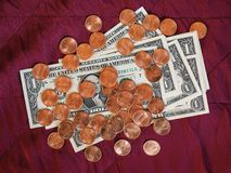 Billetes y moneda, Estados Unidos del dólar sobre fondo rojo del terciopelo imagen de archivo