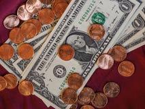 Billetes y moneda, Estados Unidos del dólar sobre fondo rojo del terciopelo Imagenes de archivo