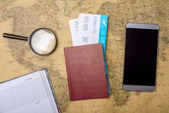 Billets d'avion avec le passeport et le téléphone sur le fond de carte du monde, topview Le concept des transports aériens et des Photographie stock libre de droits