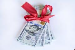 100 billets d'un dollar avec le ruban rouge sur un fond blanc Images stock