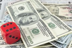 Billets d'un dollar empilés et un grand cube rouge Photographie stock libre de droits