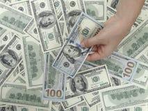 100 billets d'un dollar et 1 fond de main Image libre de droits