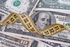 Billets d'un dollar et ruban métrique jaune Images stock