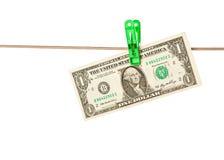 Billets d'un dollar goupillés à une corde à linge Image stock