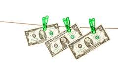 Billets d'un dollar goupillés à une corde à linge Photo libre de droits