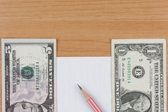 Billets d'un dollar, papier de note et crayon sur la table en bois photo stock