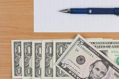 Billets d'un dollar, papier de note et stylo sur la table en bois photo stock