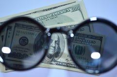 100 billets d'un dollar par les lunettes du soleil Images stock