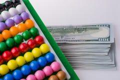 Billets de banque américains du dollar par le côté d'un abaque coloré Photo libre de droits
