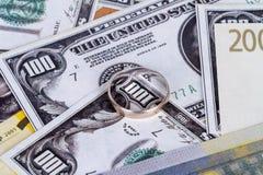 Billets de banque avec l'anneau de mariage dans le concept de finances Photo libre de droits