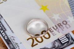 Billets de banque avec l'anneau de mariage dans le concept de finances Photographie stock libre de droits