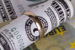 Billets de banque avec l'anneau de mariage dans le concept de finances Photo stock