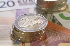 Billets de banque avec 2 piles de 2 euro pièces de monnaie Images stock
